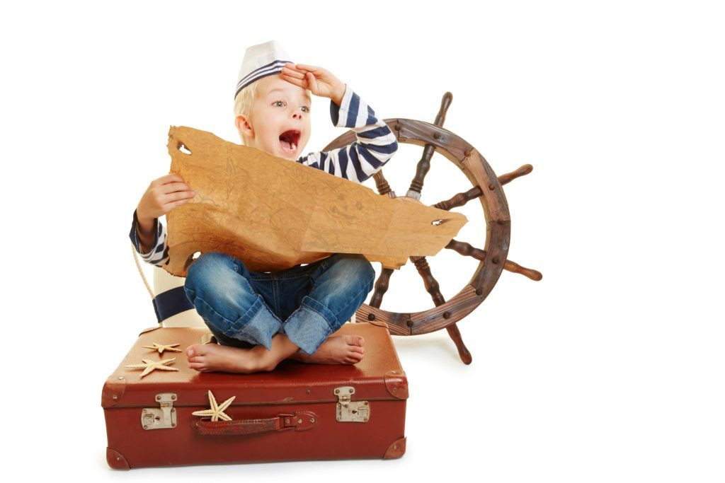 kid sitting on a suitcase with a pirate map and pirate wheel playing a game