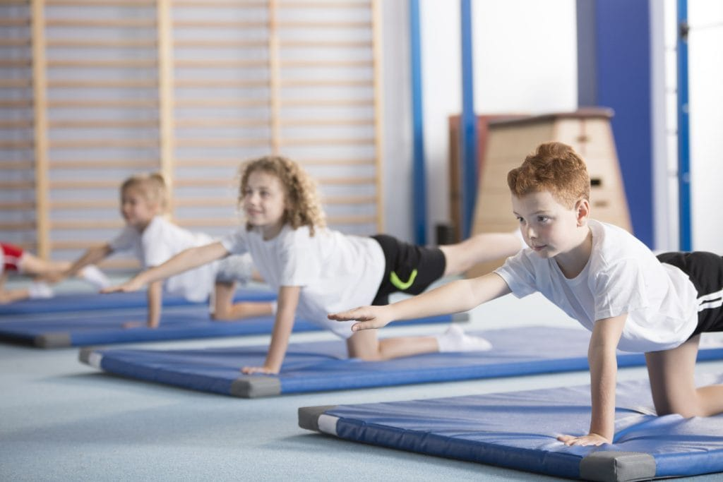 Three kids balance on one knee and opposite hand in a gymnasium on mats
