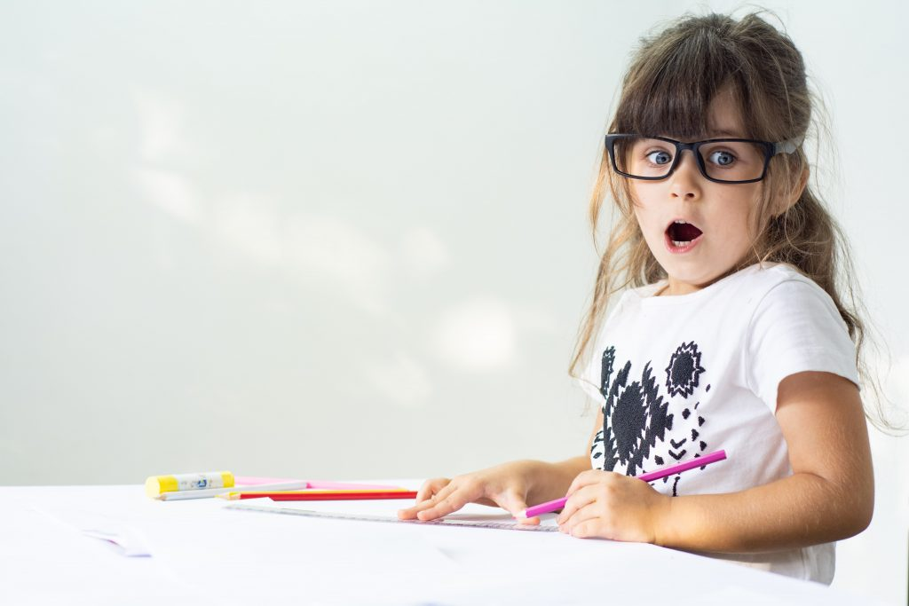 A lyoung student is coloring with pencils on a write paper while looking shocked and looking at something out of the frame