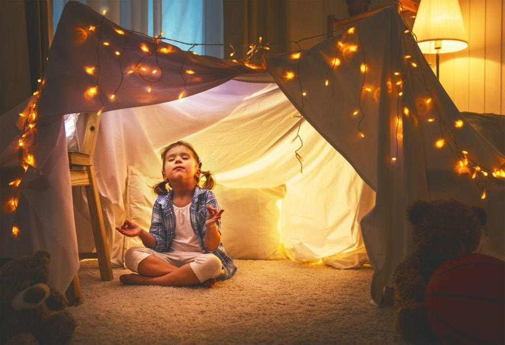 child girl playing meditates in yoga pose in tent at home before going to bed, mindfulness activities for kids, simple mindfulness activities