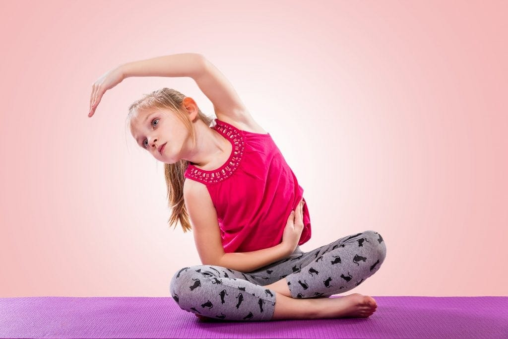 Little girl sitting in yoga pose over color background, reaching one arm up and over in an arch