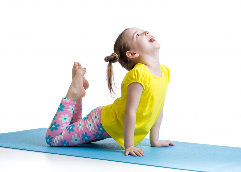 girl doing a modified swan or king cobra pose on yoga mat in class