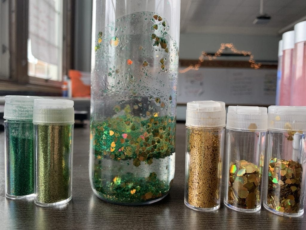 how to make a glitter calm down jar, first add glitter, then a little water to swirl it up