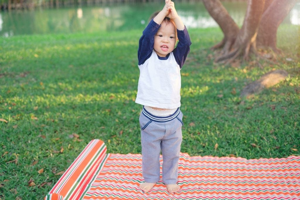 mindful toddler lifting arms while outside practing a yoga mindfulness meditation game on a bright mat