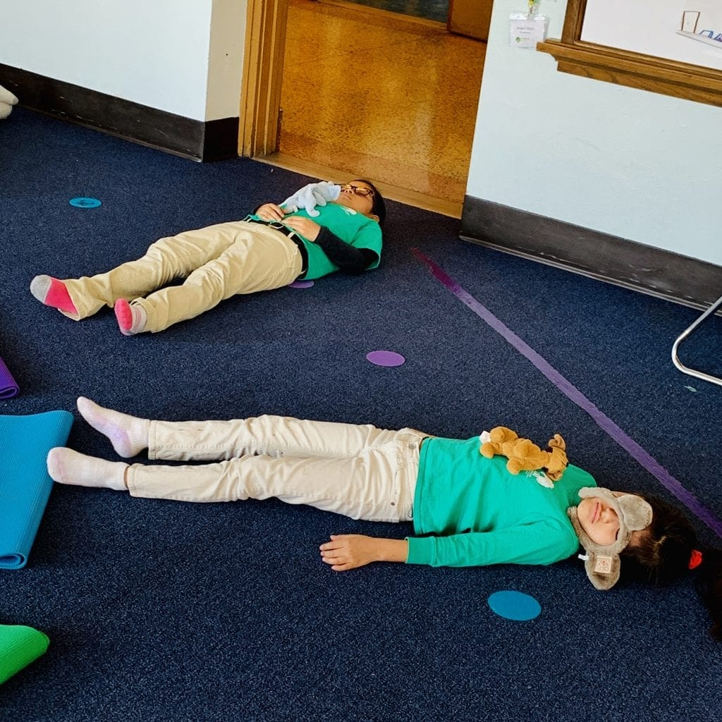 mindful students resting in a savasana pose and breating deeply with an animal on their tummy