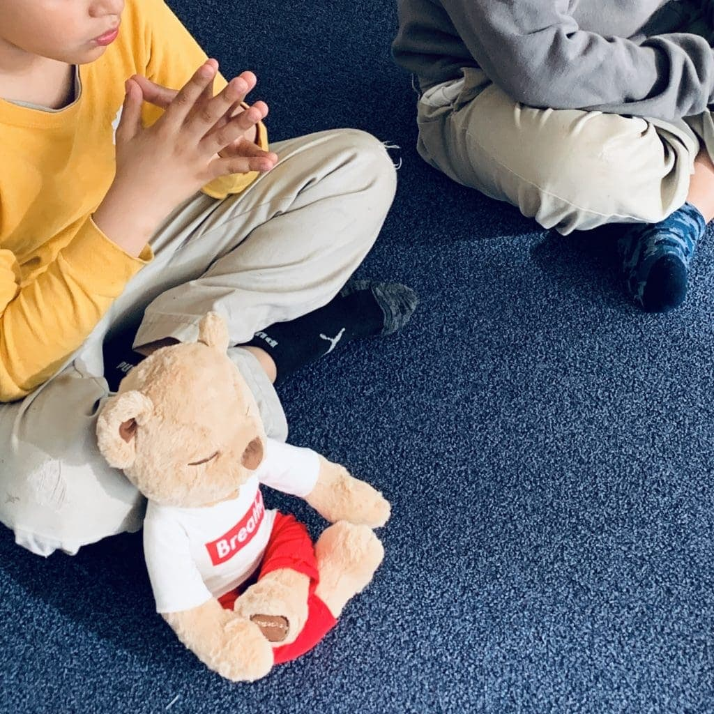Meddy teddy is sitting next a student practicing mindful breathing and meditation
