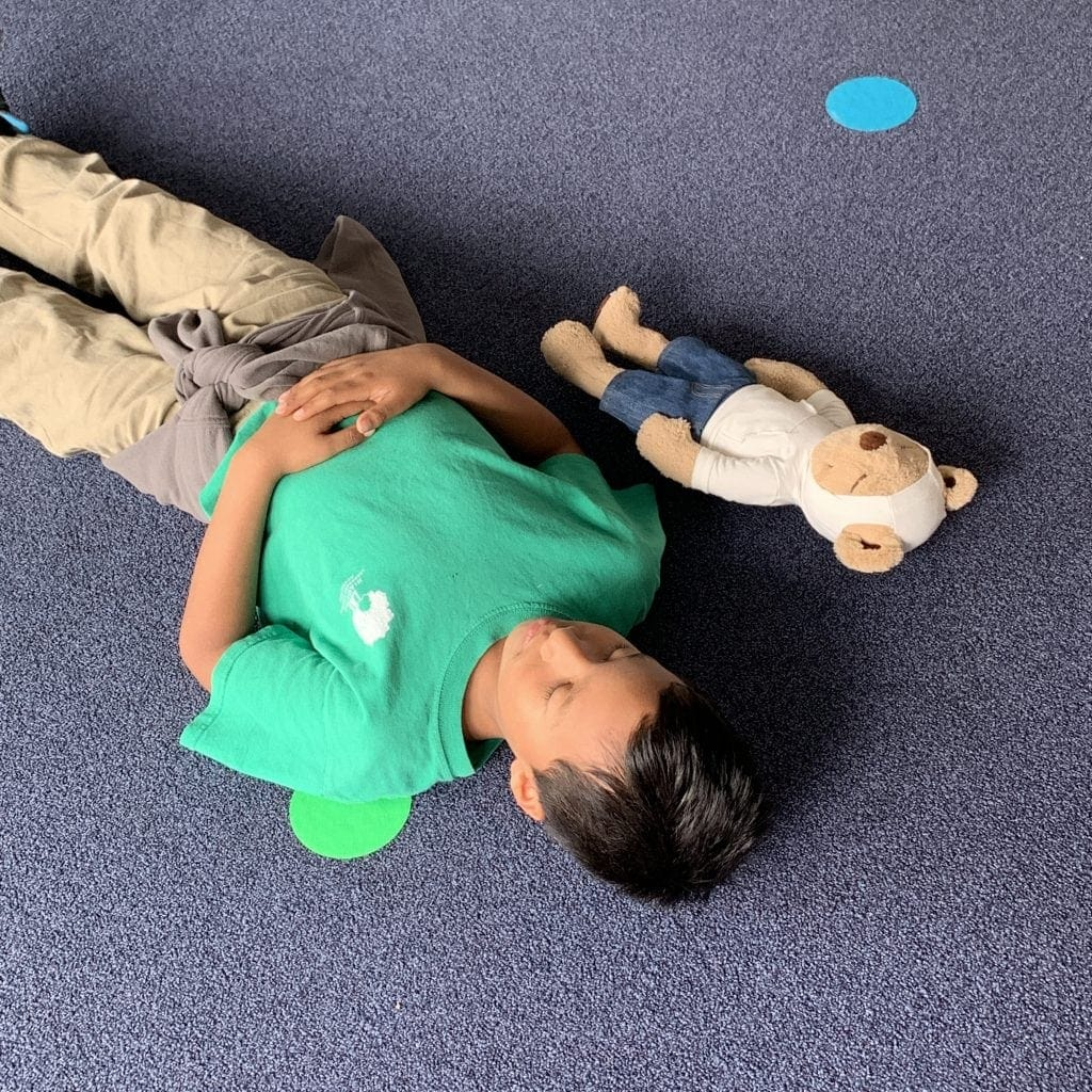 Meddy Teddy and a student are resting calmly during savasana