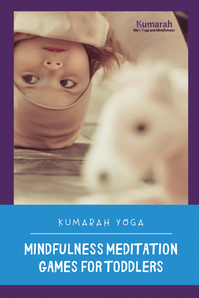 Toddler doing down dog pose practicing a mindfulness meditation game with a stuffed animal