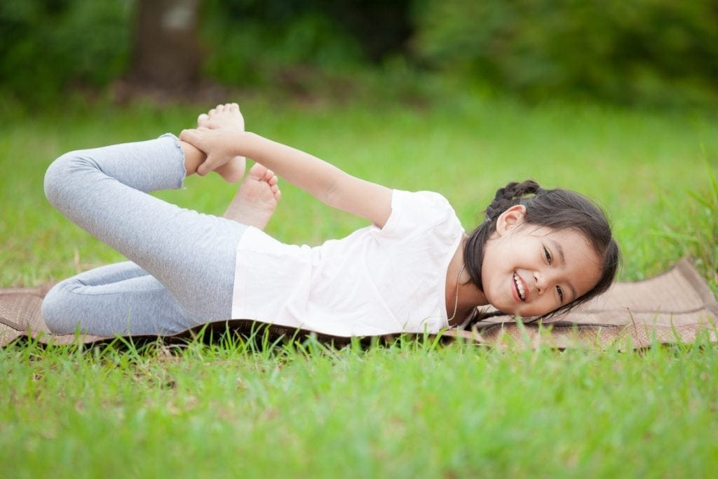 girl doing half bow pose on a yoga mat in a park, kids yoga classes