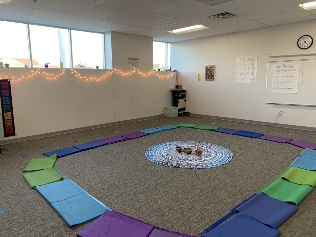 kids yoga class with folded mats, colored tape, circle spots, beautiful circle mandala cloth, singing bowl, calming breathing ball