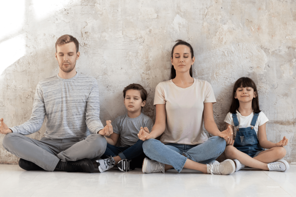 a family sitting and meditating with eyes closed and fingers in a mudra on their knees